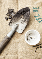 Gardening tools soil and pot plant on sack background