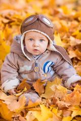 Cute baby in autumn leasves.