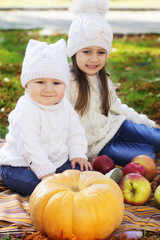 Baby boy with sister in autumn park