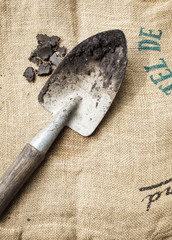 Gardening tools and soil on sack background