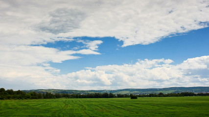 Moving cumulus clouds over green field, full  HD time lapse.