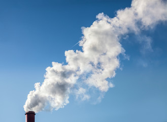 Smoke from industrial smokestack on a clear blue sky.
