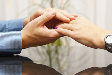 Man's hand caresses a woman hand. Lovers and dating concept