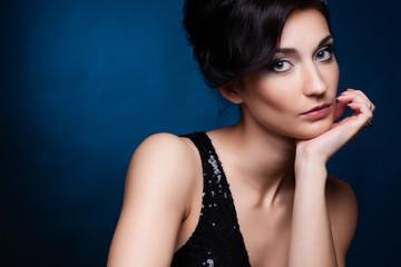 Portrait of beautiful brunette woman in black dress.