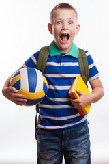 Happy schoolboy with backpack, ball and books