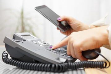 Woman is dialing on land line phone and looking on mobile phone