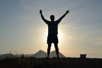 Турист на горе, тень силуэта на солнце