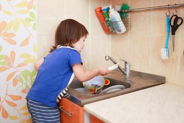 2 years boy washing dishes