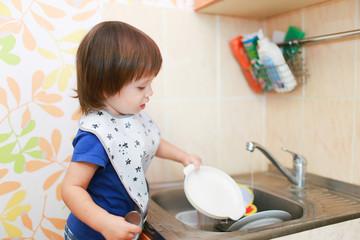 lovely little boy washing dishes