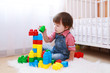 lovely toddler playing constructor at home