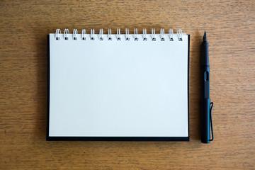 notebook and black pen on wood desk