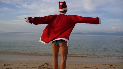 Woman on the Beach in Santa Claus Suit. Slow Motion.