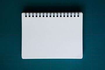 notebook on blue cutting mat