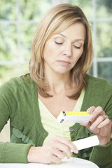 Woman Reading Information On Drug Packaging