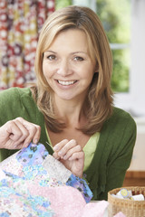 Portrait Of Woman Sewing Quilt At Home
