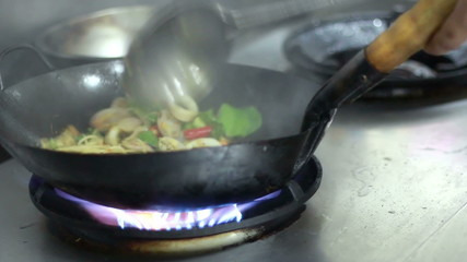 chef cooking spicy seafood spaghetti in kitchen