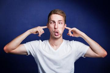 junger Mann steckt sich finger in die ohren um nichts zu hören