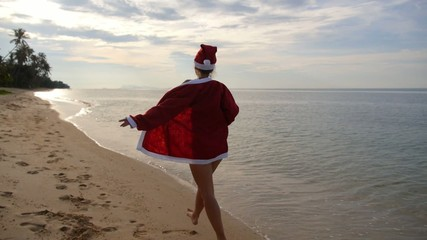 Young Sexy Santa Claus in Bikini Running on Beach. Slow Motion.