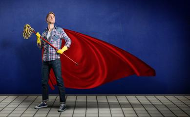 Student mit wischmopp in der Hand posiert wie ein Superheld