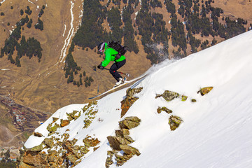 Woman skier jumping over a cliff in the mountains