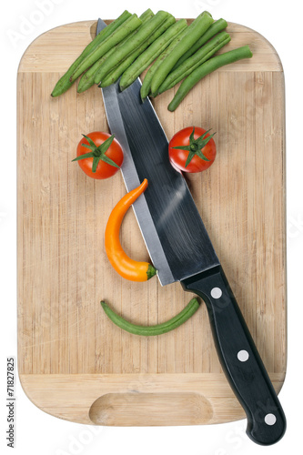 canvas print picture Essen schneiden mit Messer Gesicht aus Gemüse auf Küchenbrett