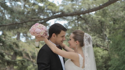 Young newlyweds are in the park and with tenderness and love