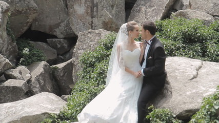 Newlyweds affectionate to each other among the rocks
