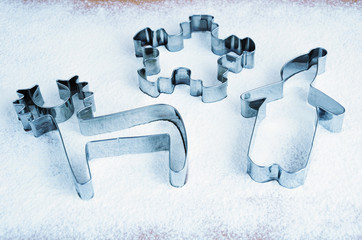 toned cold colors cookie cutters on the table with flour