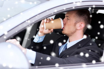 close up of man drinking coffee while driving car