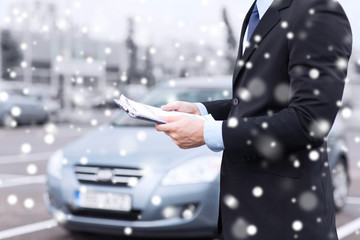 close up of man with clipboard and car documents