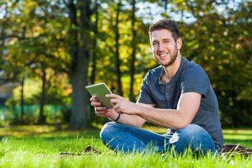 Mann im Park mit Tablet