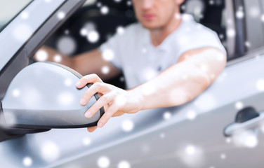 close up of man adjusting car sideview mirror