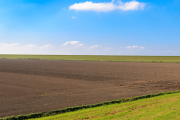 Ploughed field with protective dike in East Frisia, Germany
