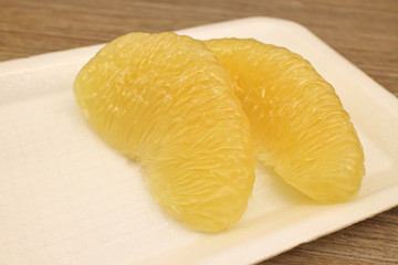 Pomelo pieces on white tray. Healthy fruit background.