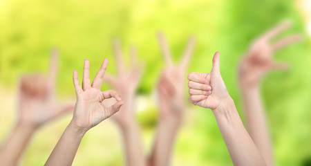 People show different hands signs on green background
