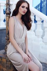 girl with dark hair and blue eyes in elegant beige dress