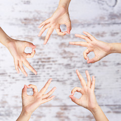 Young people's hands on wooden background