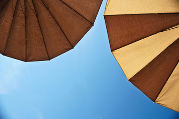 Two brown parasols under blue skies. Beach background. View from