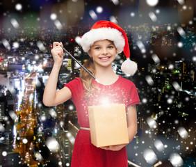 smiling girl in santa helper hat with gift box