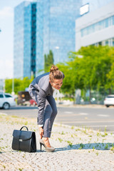 Business woman in office district having pain in leg