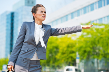 Concerned business woman in office district catching taxi