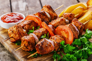 meat skewers with potatoes on the board