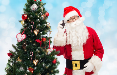 santa claus with smartphone and christmas tree