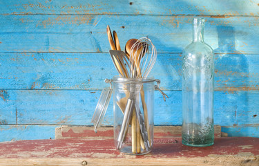 vintage kitchen utensils, wooden spoons and an old ornamented bo