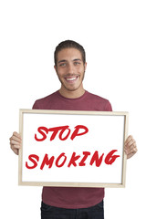 happy young man showing board with text: Stop smoking campaign