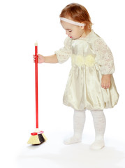Little girl tidying sweeping the floor