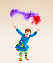 little girl shows up colorful tinsel.
