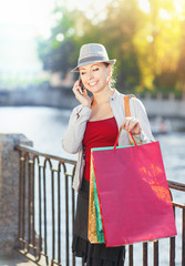 Beautiful girl with shopping bags talking on the mobile phone