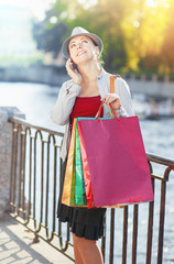 Beautiful girl with shopping bags talking on the mobile