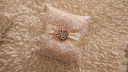 Gold wedding rings lie on a beautiful cushion